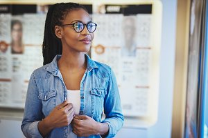Satisfied young woman wearing eyeglasses at store