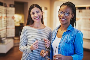 Laughing diverse friends choose new glasses