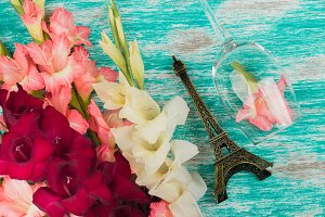 Light pink and red gladiolus and wineglass on the azure background