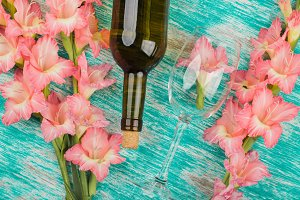 Light pink gladiolus, wineglass and bottle of wine on the azure background