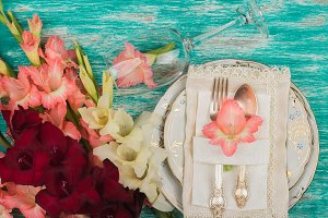 Tableware and silverware with light pink gladiolus on the azure background