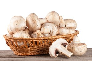 Champignon mushrooms in a wicker basket on a wooden table with white background