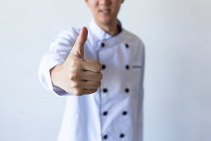 Smiling chef showing thumbs up with white copy space (focus on hands)