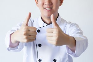 Asian chef showing thumbs up over white background