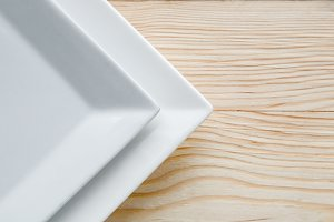 Square white plates over wooden tabl