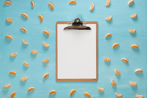 Blank clipboard on pastel blue color table with citrus tangerine slices, minimal style, flat lay