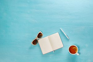 Flat lay composition of diary, glasses, pen and cup of tea on blue wooden desk