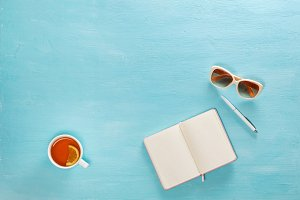 Opened notebook with pen, cup of tea and sunglasses on blue wooden table. Top view. Writing, blogging concept