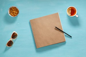 Flat composition of sketch book, pensil, sunglasses and saucer with almonds