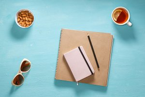 Flat composition of sketch book, pink diary, pensil, sunglasses and saucer with almonds