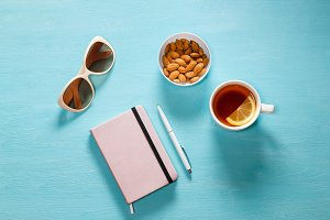 Blue desk with pink notebook, white pen, cup with tea, almonds, glasses. Feminine workspace, flat lay.