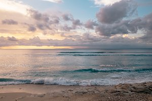 Tender sunset at a fantastic sea beach with soft pink clouds in Bali. Exotic tropical nature of Indonesia sea shore, waves and orange sunset on horizon, outdoor summer nature landscape