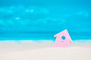 Symbol of little lilac house on the sand with bright cloudy blue painted sky background