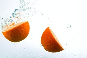 Orange in streams of water on a white background