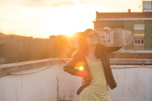 Beautiful young woman with skateboard backlit at sunset