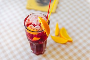 Red cocktail with straws and orange wedge in high glass