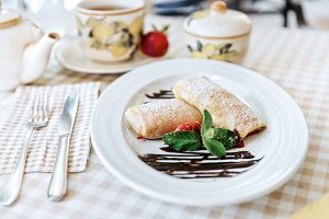 Pancakes with chocolate, fresh strawberry and mint
