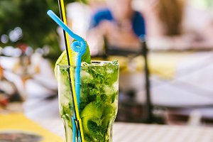 Mojito with straws and lemon wedge in high glass