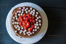 Delicious cake with fresh strawberries and dark chocolate decoration