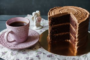 Delicious cake in chocolate sauce with cup of tee