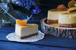 Christmas cake with cinnamon and it's slace, orange under Christmas tree