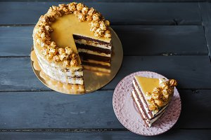 Delicious cake with caramel popcorn and caramel sauce
