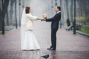 Wedding couple whirls in the park