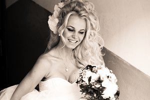 Blonde bride smiles with bouquet