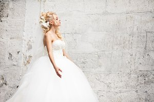 Curly blonde bride behind a wall