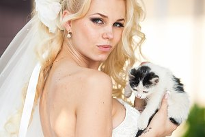 Sexy curly bride holding a kitty