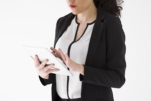Businesswoman working with a tablet on neutral background