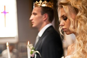 Curly blonde bride holds a candle