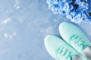 Pair of green woman canvas sneakers on blue background