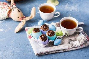 Easter sweet cup cakes treets in colorful egg shells on blue