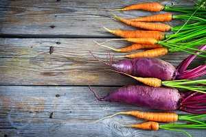 Fresh carrots and beets on a wooden background, toned. Top view