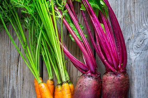 Fresh carrots and beets on a wooden background, toned