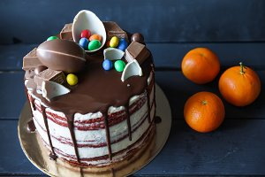 Delicious chocolate cake with chocolate candies, tangerines