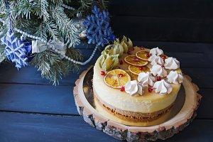 Christmas cake with cinnamon and orange under Christmas tree