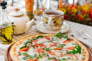 Pizza with cup of tee, on served table