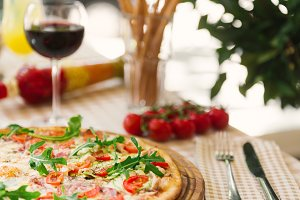 Pizza with glass of wine, on served table