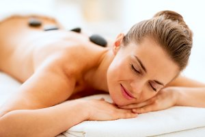 Portrait of relaxed young woman receiving hot stone massage