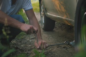 Close up view of man changes broken wheel of a car in the woods