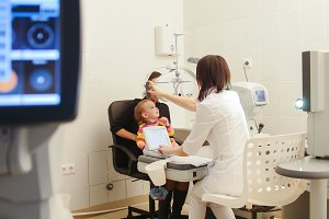 Optometrist in ophthalmology clinic checking little child's vision