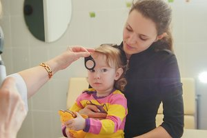 Woman optometrist in clinic checks eyesight at little girl - child's ophthalmology