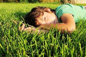 boy relaxing on green grass