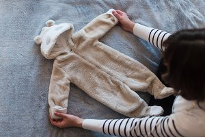 Pregnant woman dreaming and holding baby's clothes