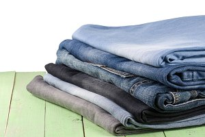 stack of jeans on green wooden background