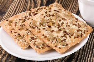 crispy bread with seeds of sunflower, flax and sesame seeds on a dark wooden background