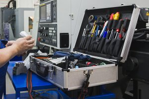 Worker in industry holding set of tools for repair - screwdriver, voltmeter, wrenches