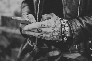 Tattooed man with smartphone